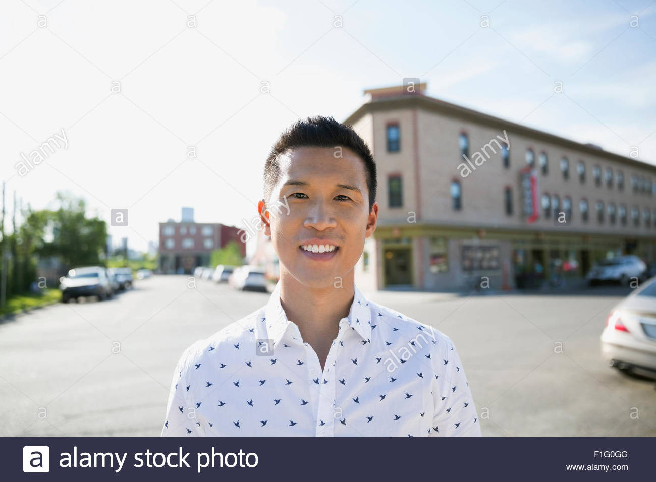 Portrait smiling man in sunny street Stock Photo