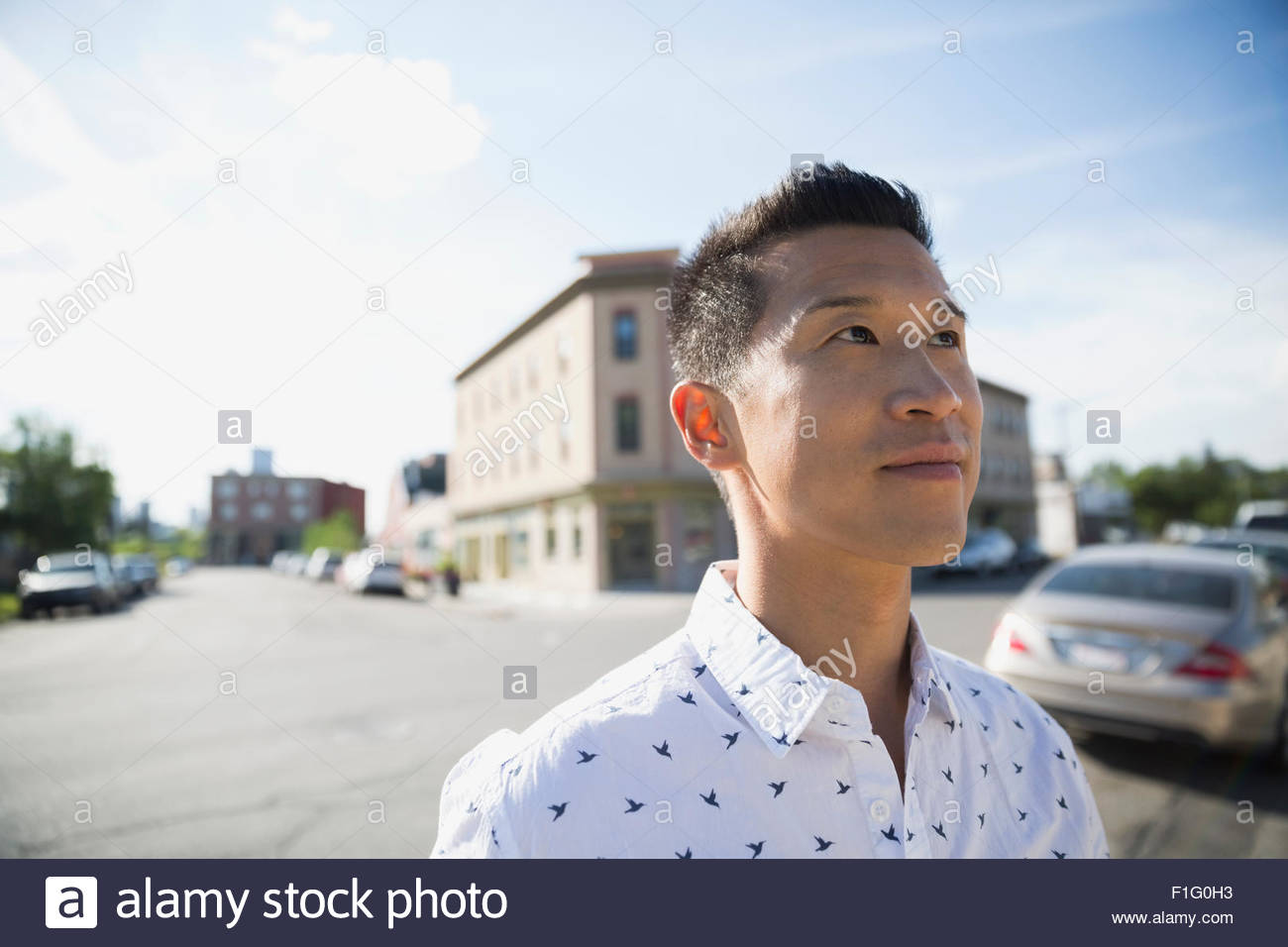 Pensive man looking up on sunny street Stock Photo