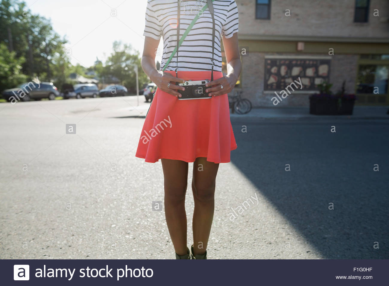 Midsection of woman in skirt with retro camera - Stock Image