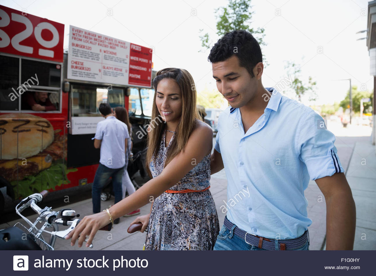 Couple with bicycle walking outside food truck - Stock Image