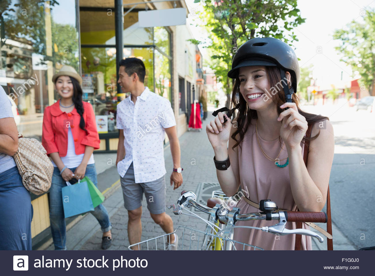 Smiling woman with bicycle putting on helmet - Stock Image