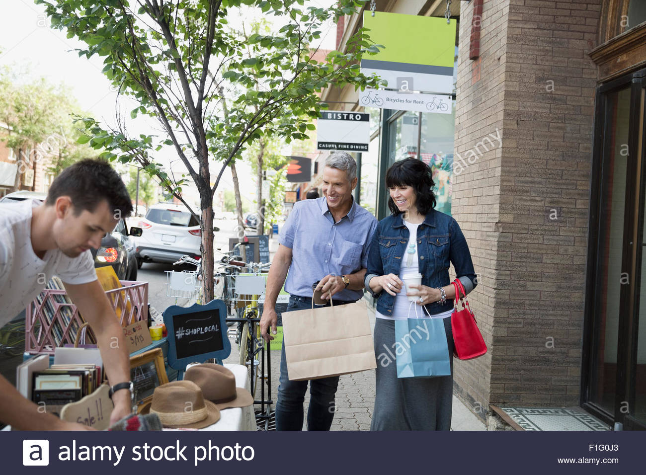 Couple with shopping bags approaching sidewalk sale - Stock Image