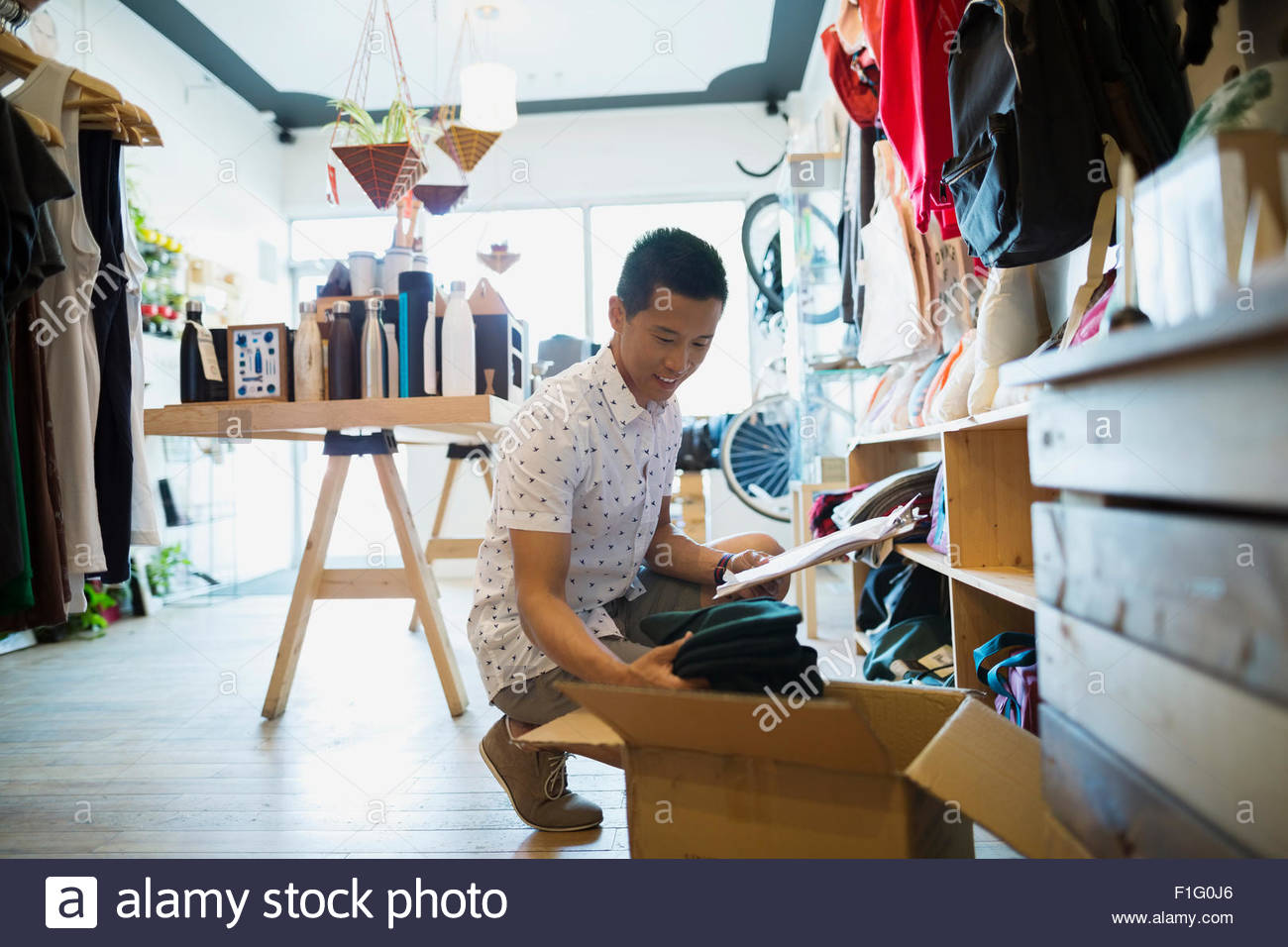 Shop owner with clipboard processing new merchandise - Stock Image