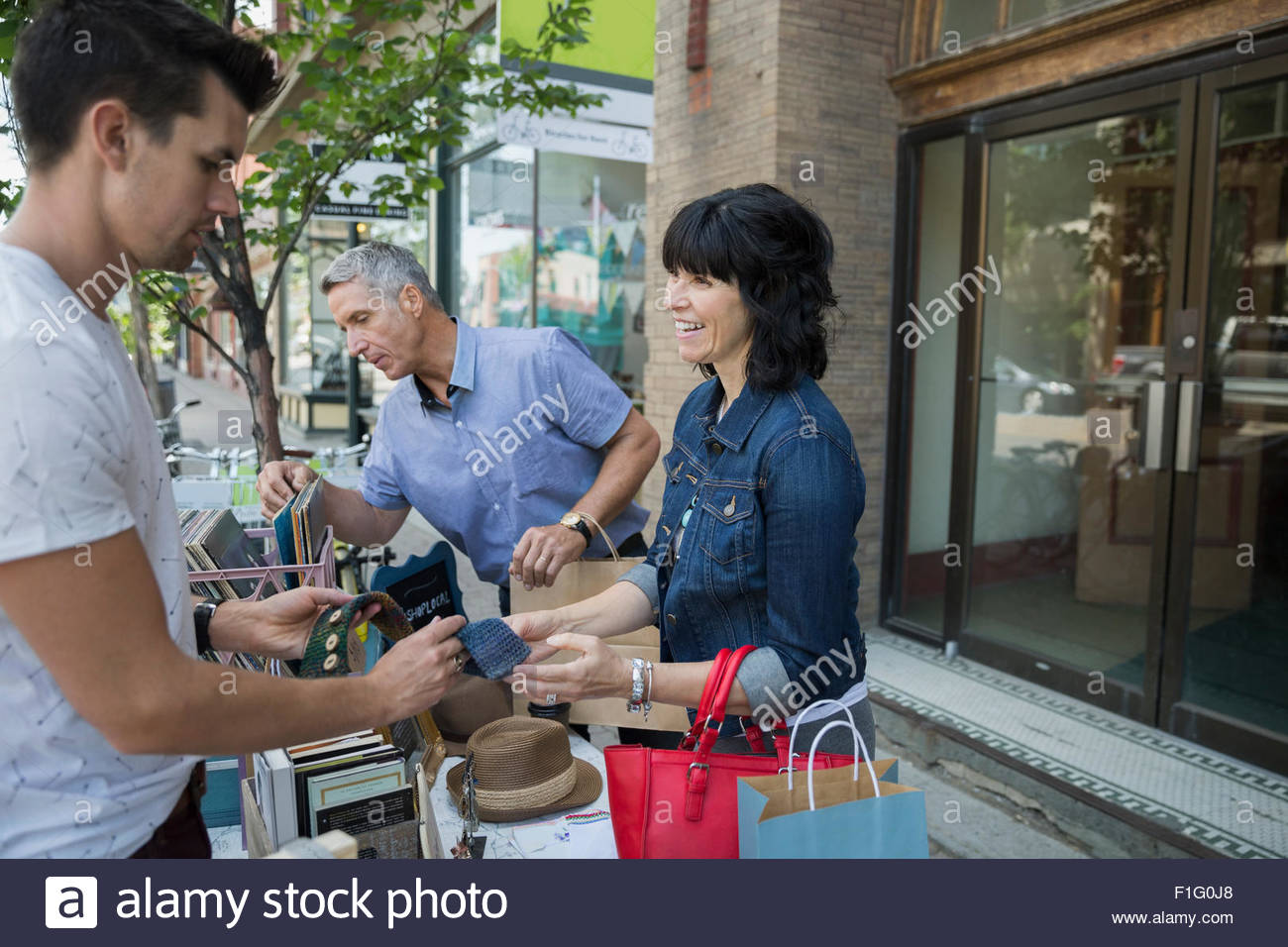 Woman shopping sidewalk sale - Stock Image