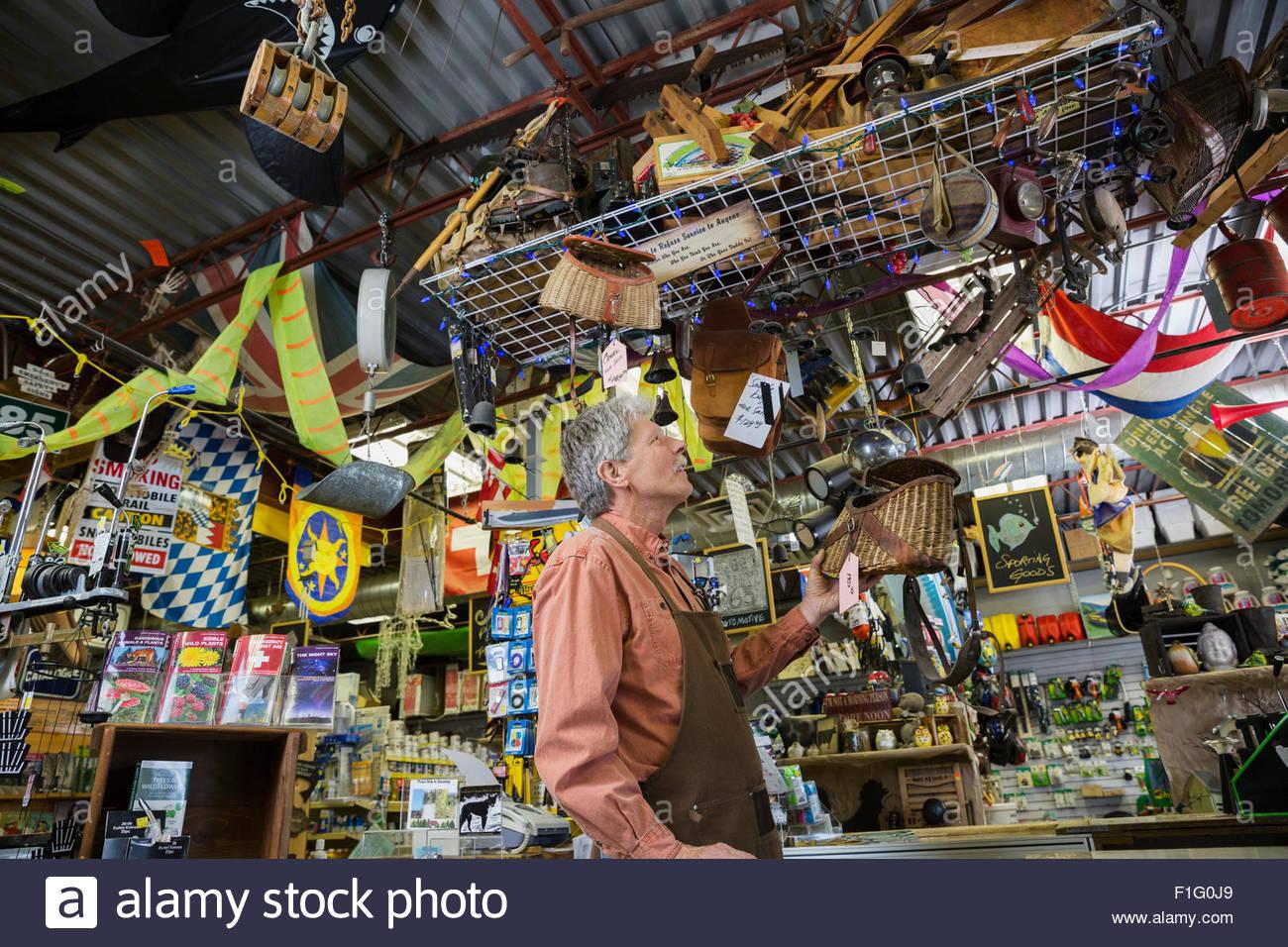 Hardware store owner checking hanging display of fishing baskets - Stock Image