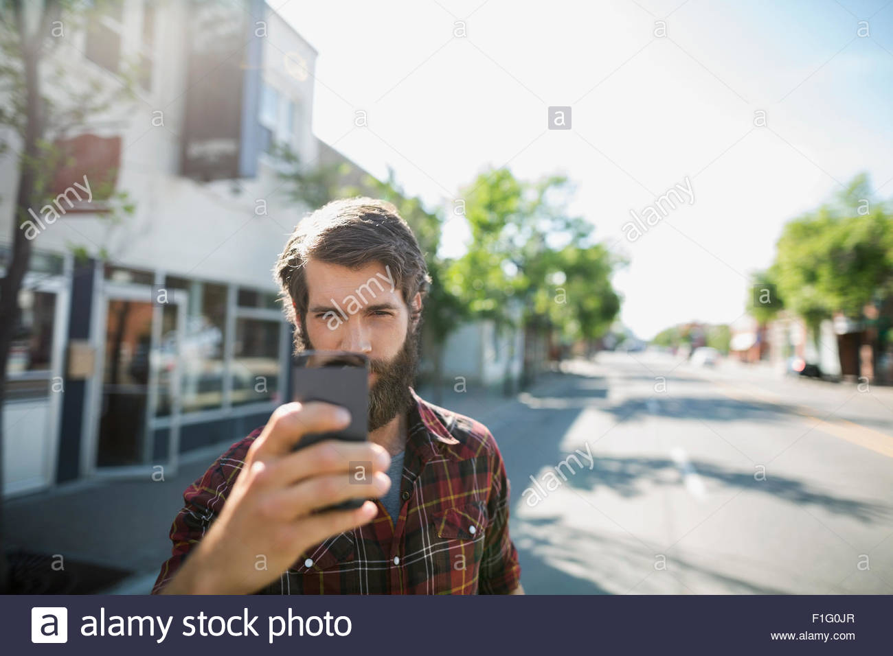 Bearded man photographing with camera phone sunny street - Stock Image