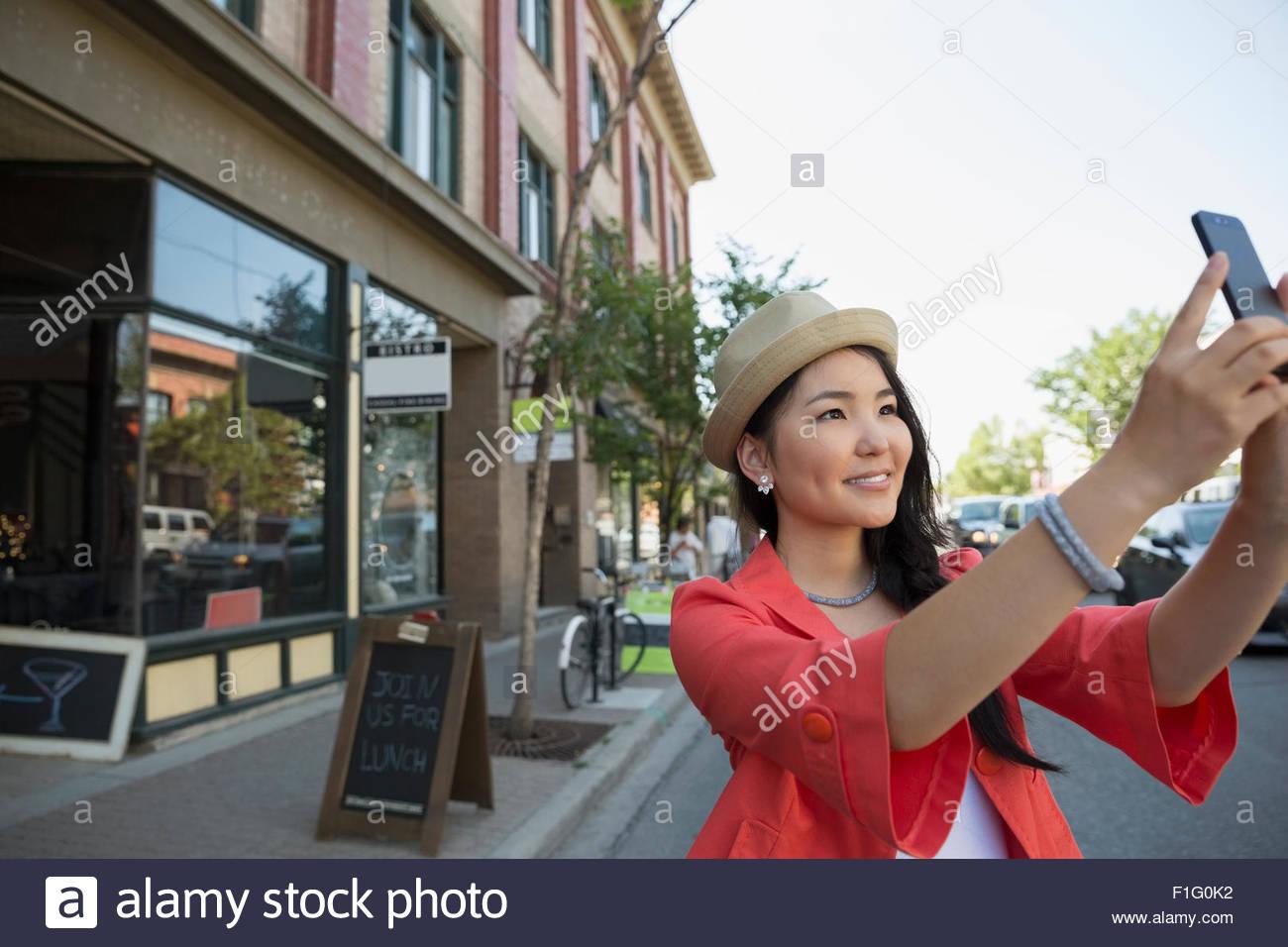 Smiling woman in hat taking selfie on urban street Stock Photo