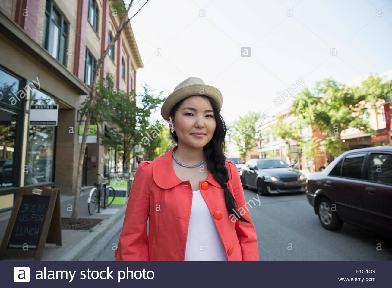 Portrait smiling woman wearing hat on urban sidewalk - Stock Image