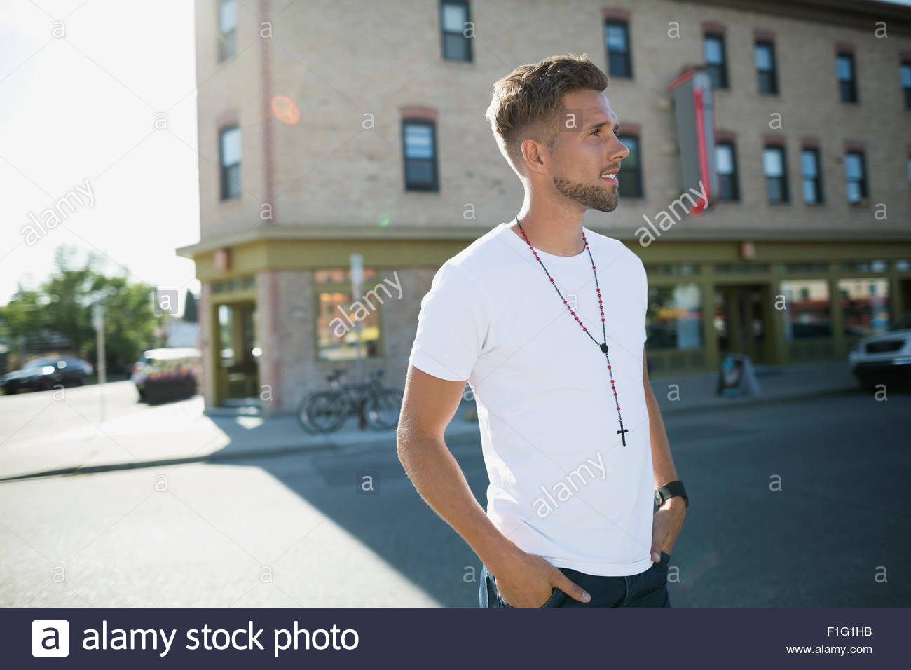 Man crossing sunny street - Stock Image