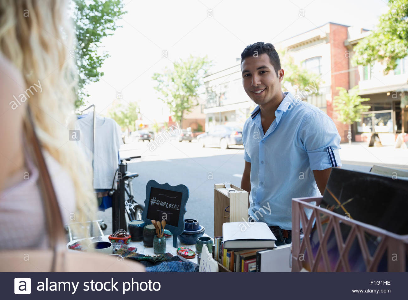 Portrait smiling man at sidewalk sale - Stock Image