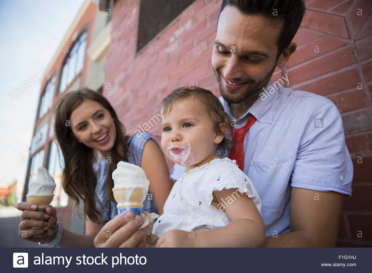 Father holding daughter with messy ice cream face - Stock Image