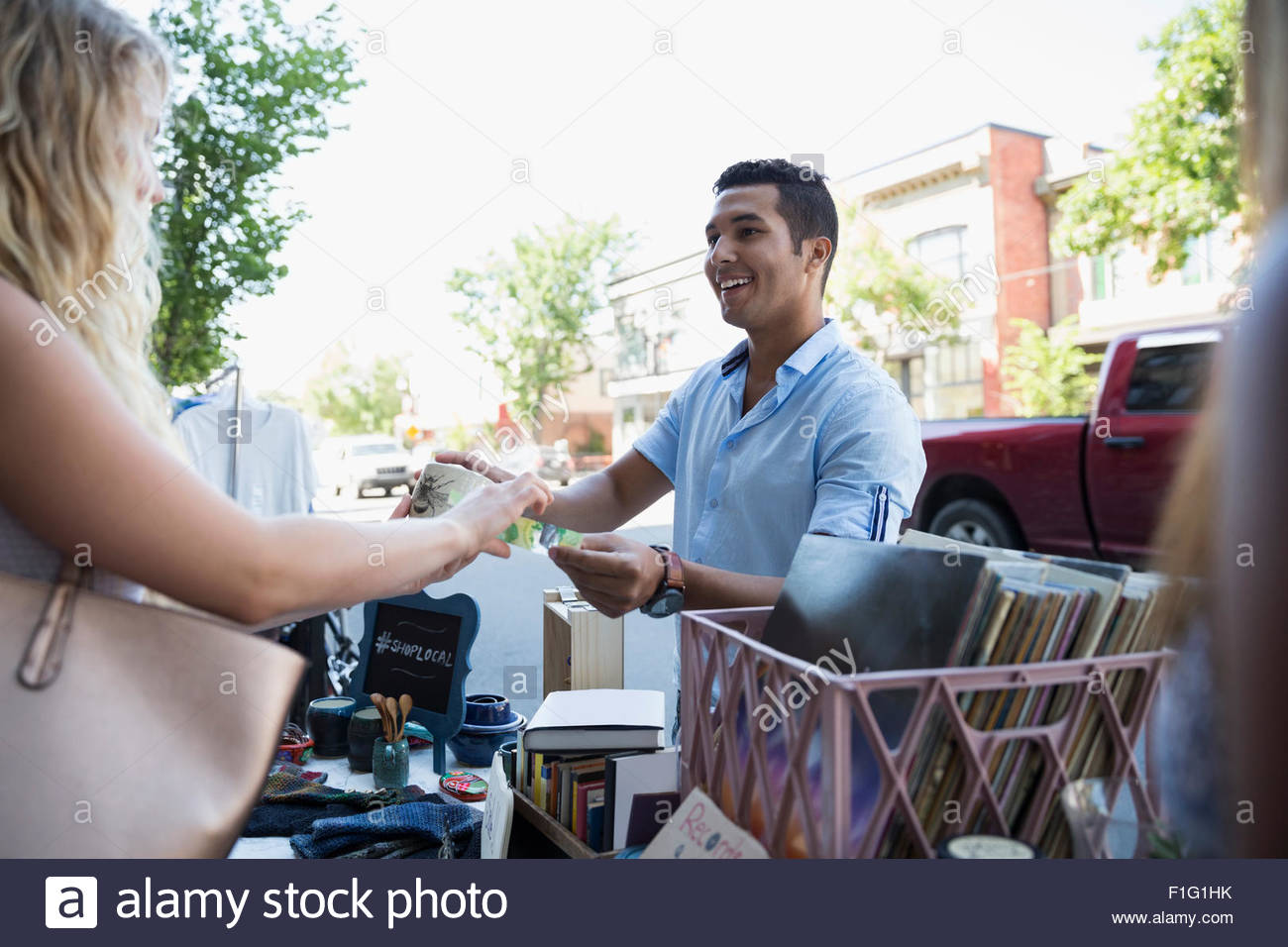 Woman paying for merchandise at sidewalk sale - Stock Image