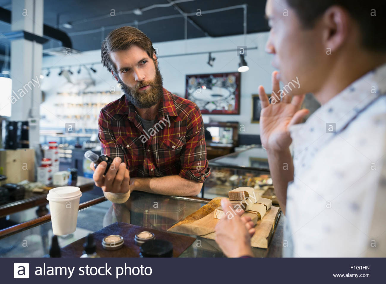 Worker explaining after shave spray to customer shop - Stock Image