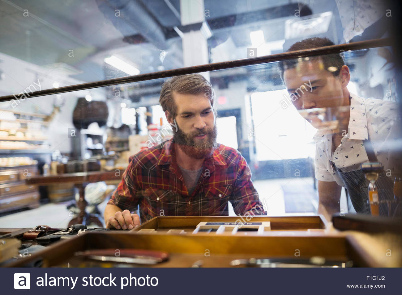 Men browsing pocketknives in display case in shop - Stock Image
