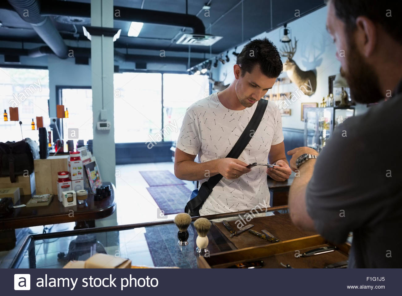 Man shopping for pocketknife in shop - Stock Image