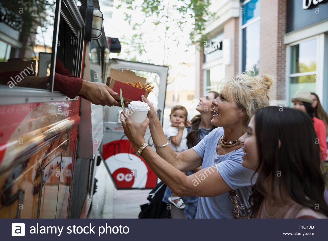 Customers receiving food outside food truck - Stock Image