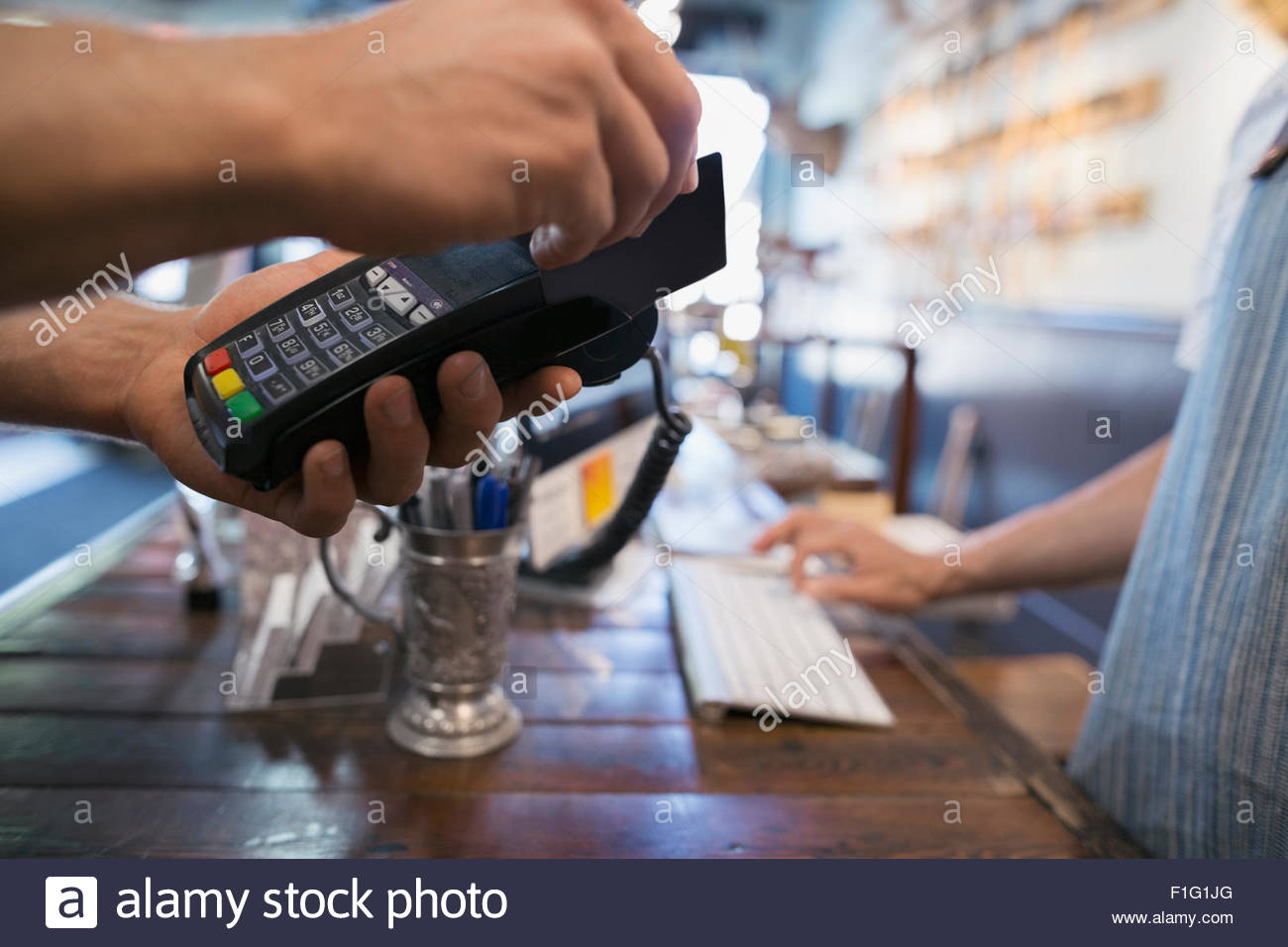 Close up man paying with credit card reader Stock Photo