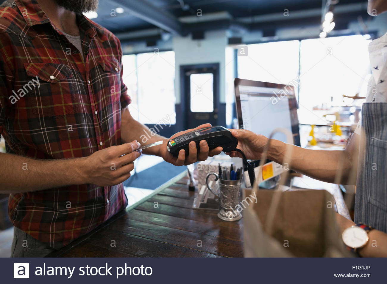 Man paying with credit card reader in shop - Stock Image