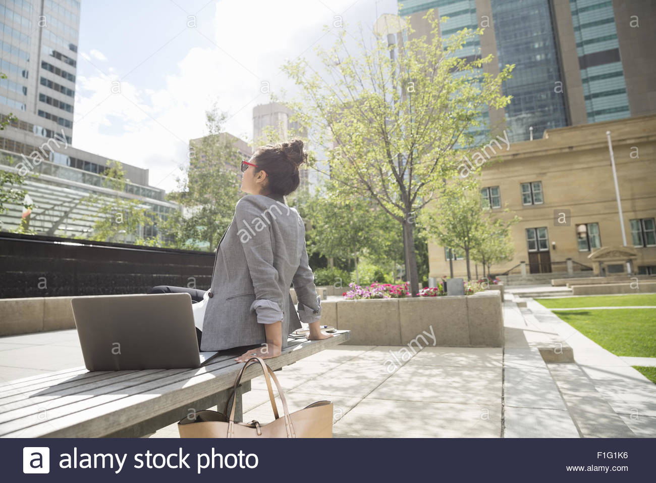 Businesswoman basking in sunshine in urban park - Stock Image