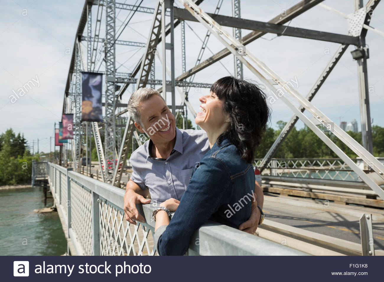Laughing couple on bridge over river - Stock Image