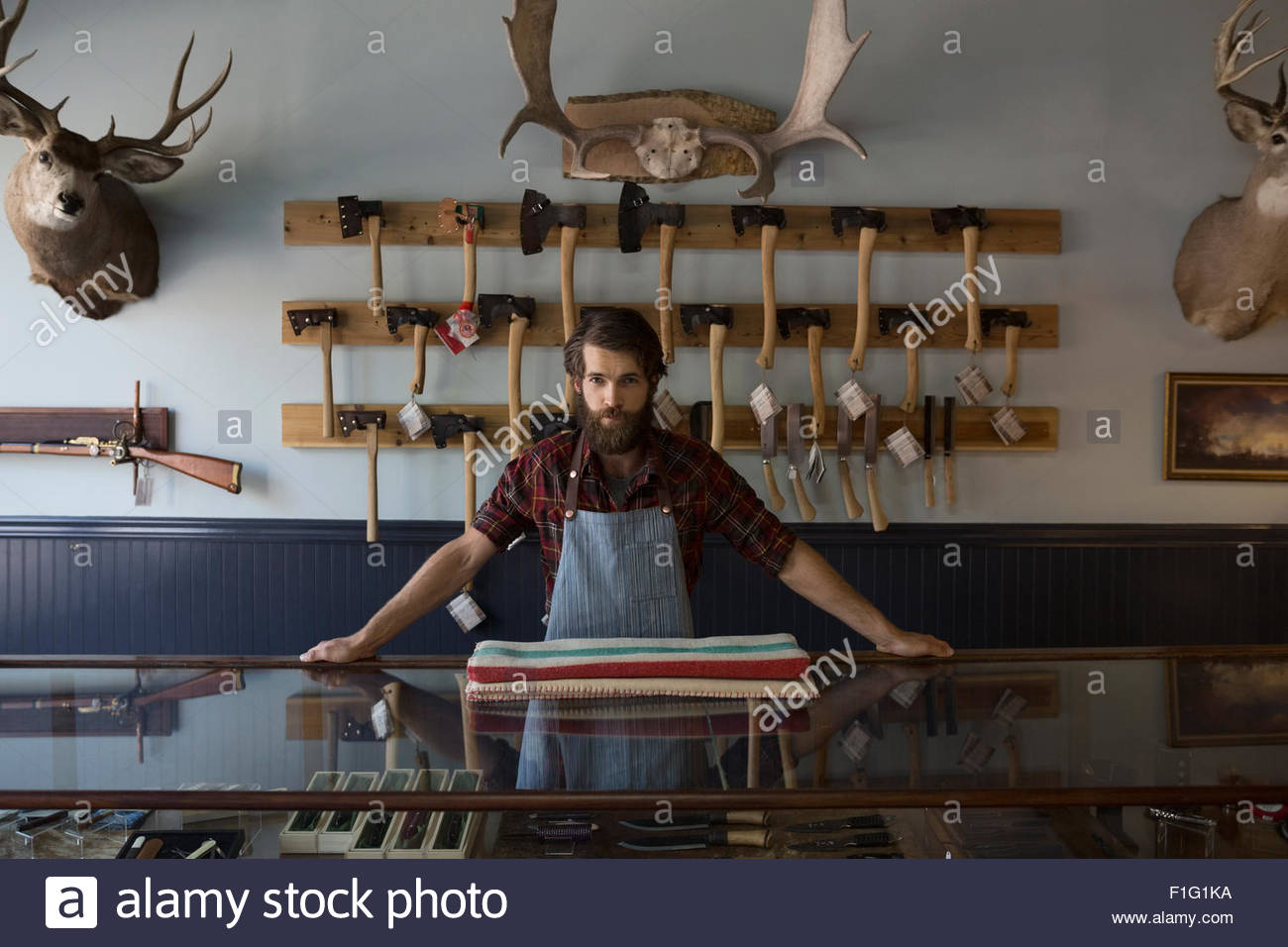 Portrait serious bearded shop worker underneath elk horns - Stock Image