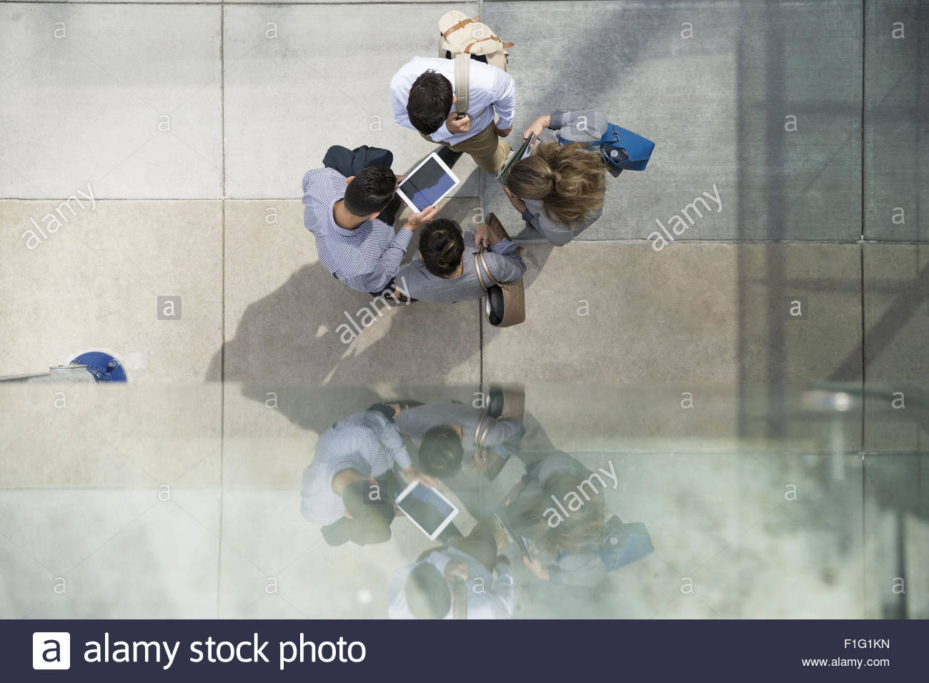 Overhead view business people using digital tablet - Stock Image