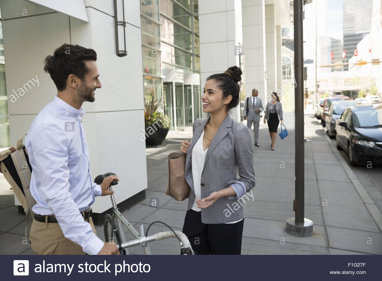 Business people talking on urban sidewalk - Stock Image