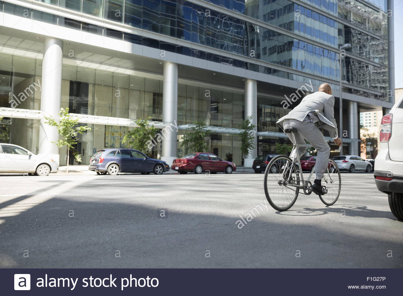 Businessman in suit riding bicycle on city street - Stock Image