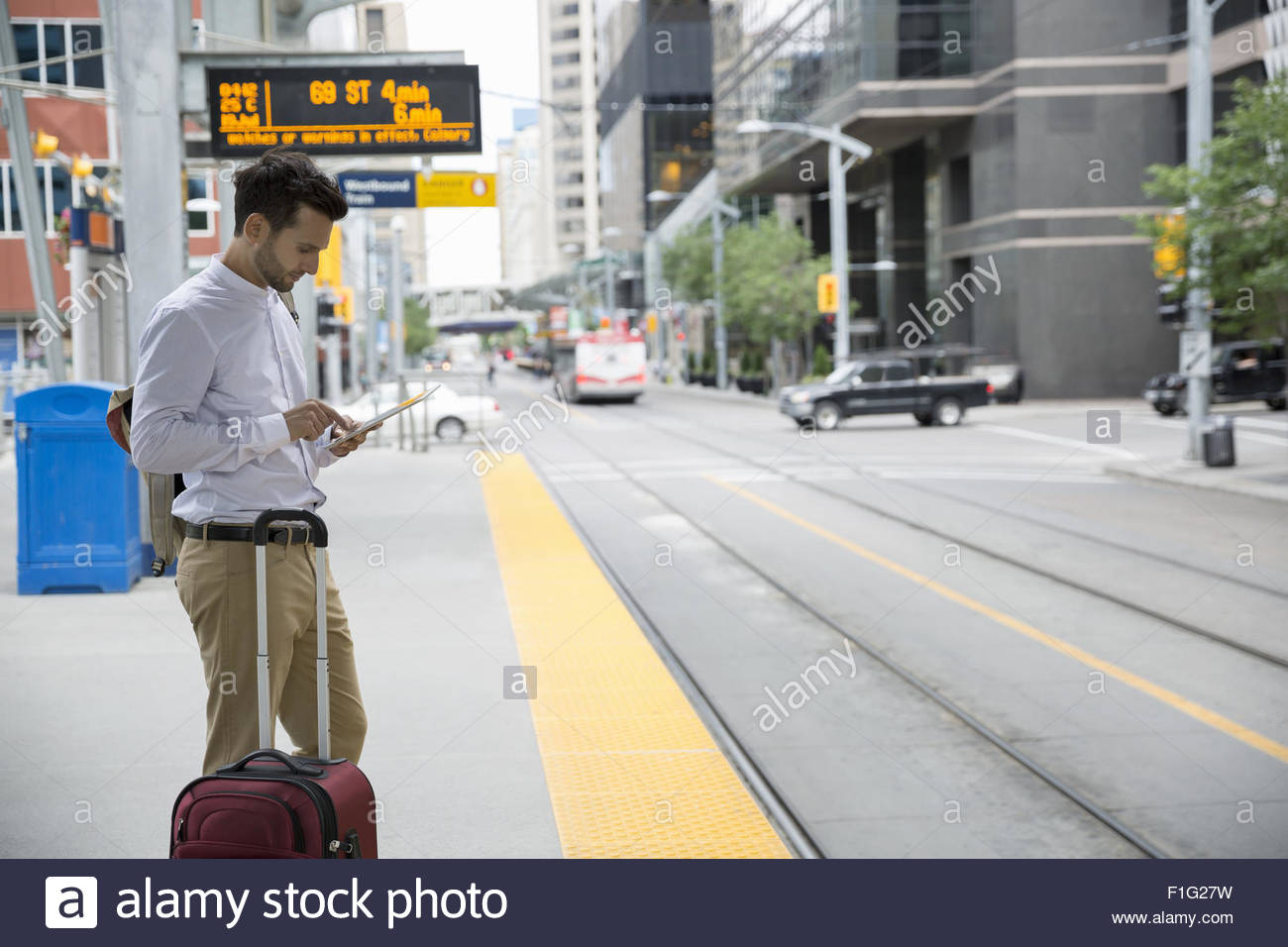 Businessman using digital tablet at train station platform - Stock Image