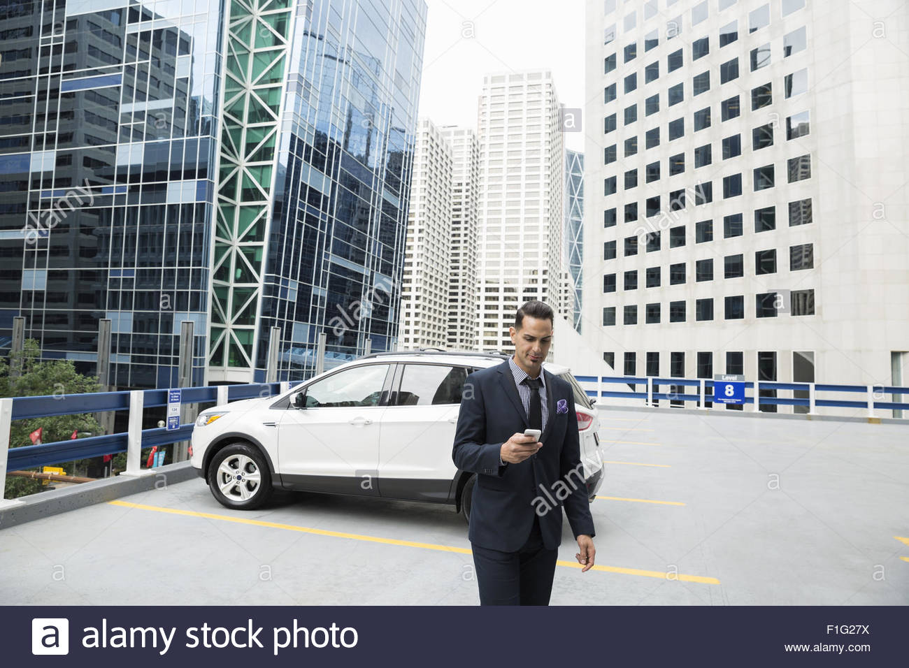 Businessman texting with cell phone city parking lot - Stock Image