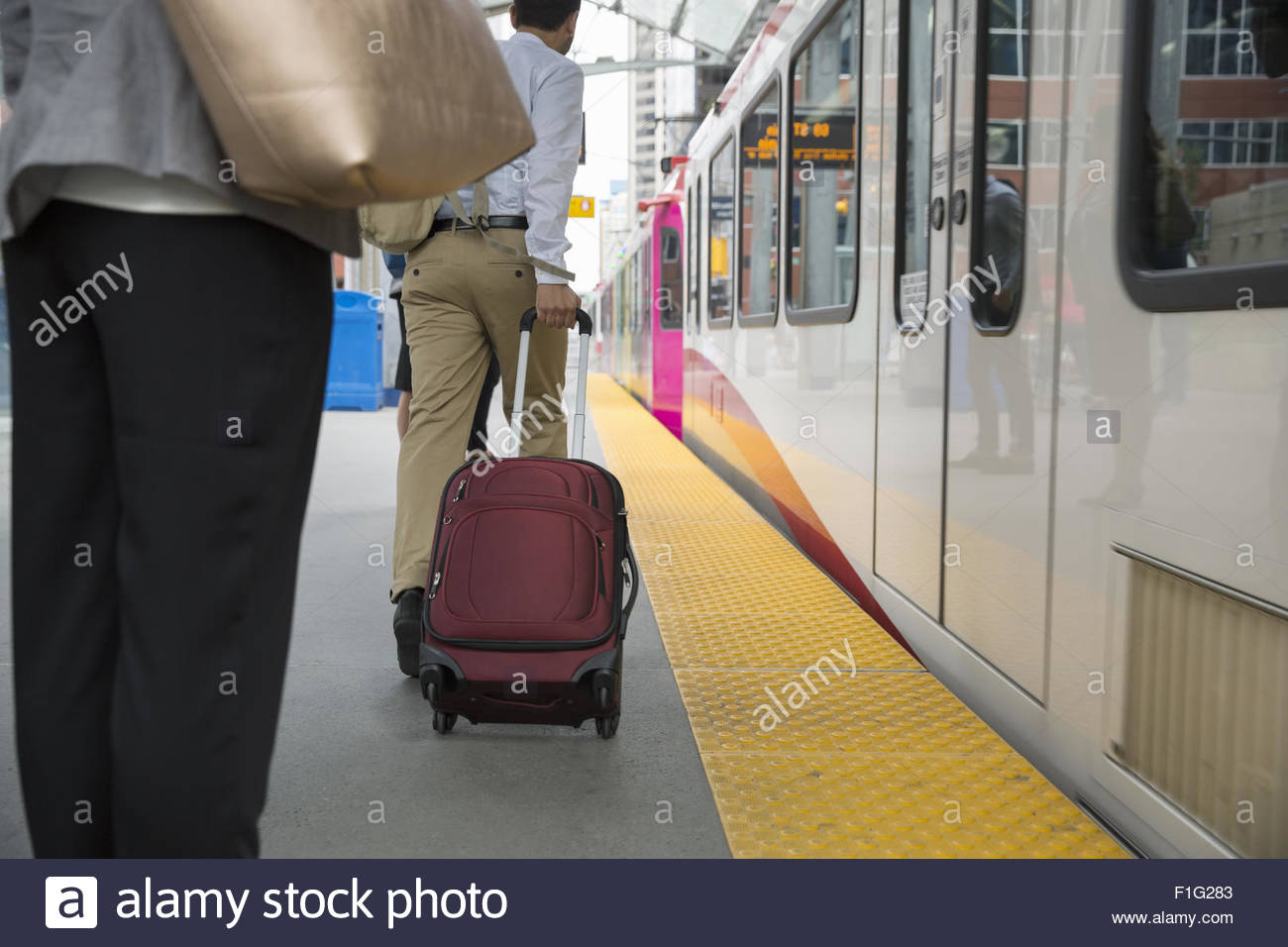 Businessman pulling suitcase along train on platform - Stock Image