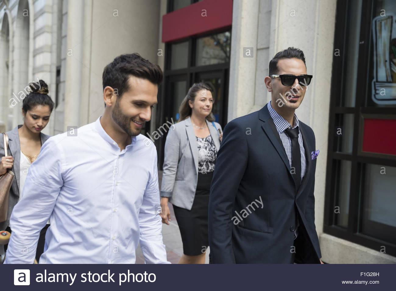 Business people walking on urban sidewalk - Stock Image