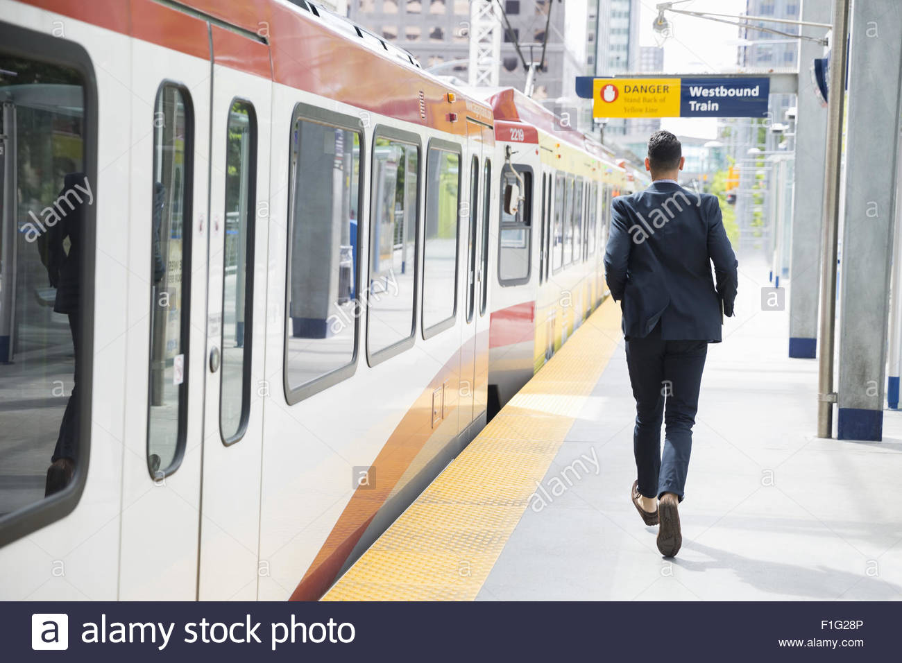Businessman running along train on platform - Stock Image
