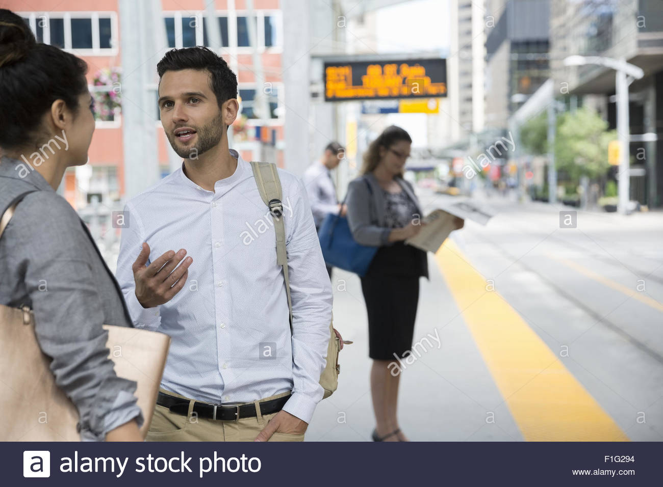 Business people talking and waiting train station platform - Stock Image