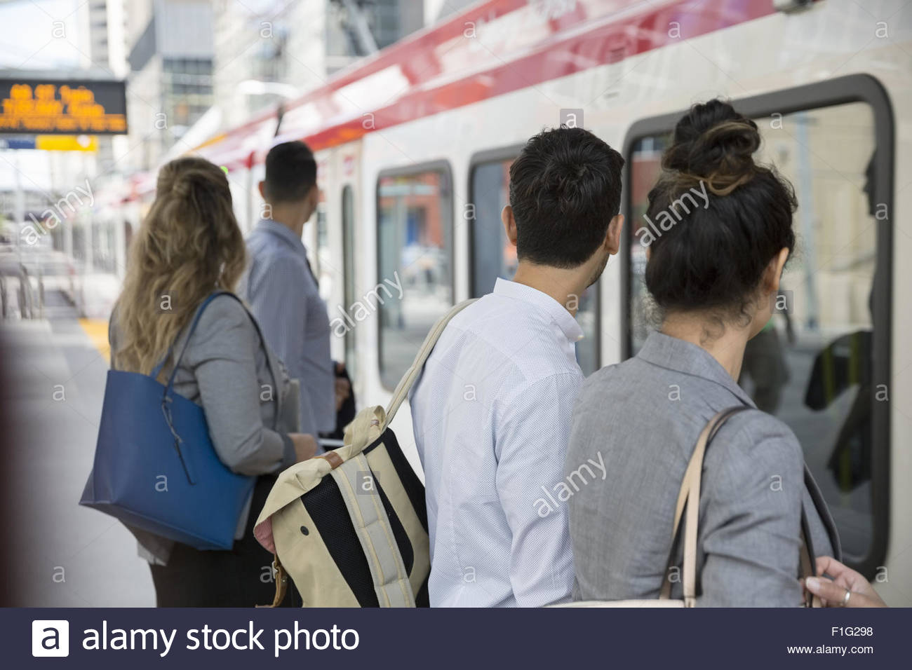 Business people waiting to board train on platform - Stock Image