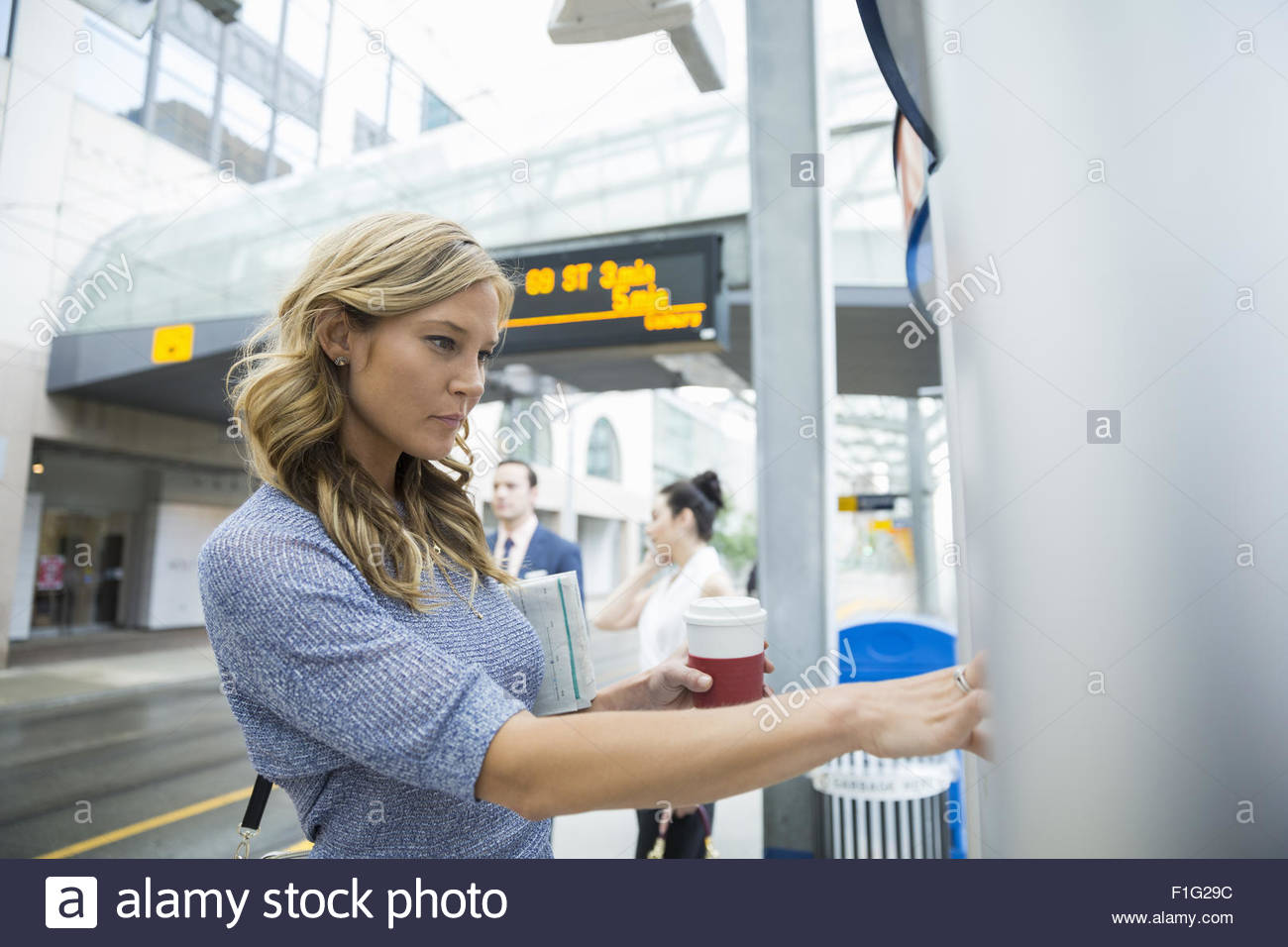 Businesswoman checking schedule at train station - Stock Image