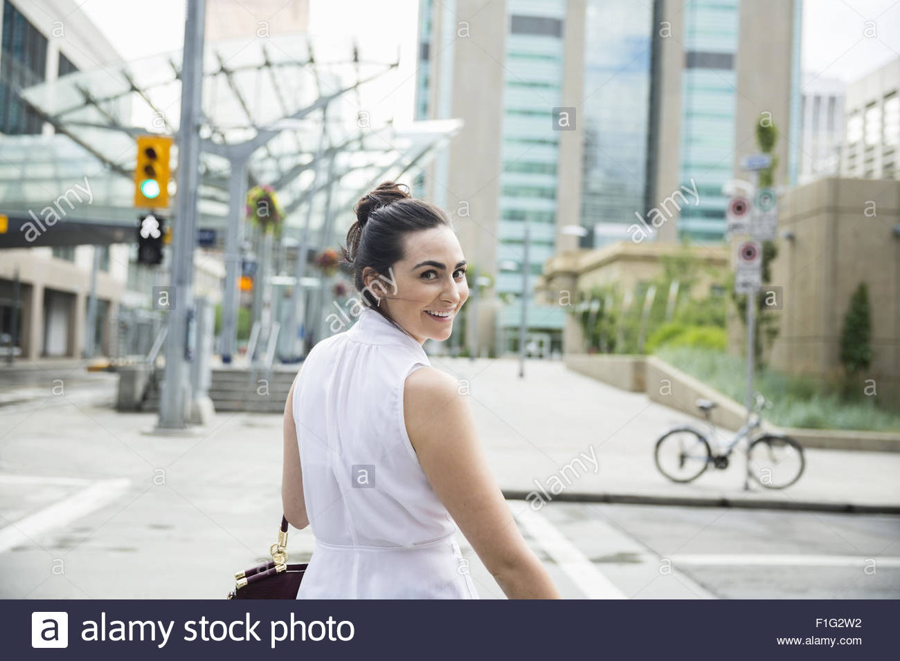 Portrait confident businesswoman turning crossing urban crosswalk - Stock Image