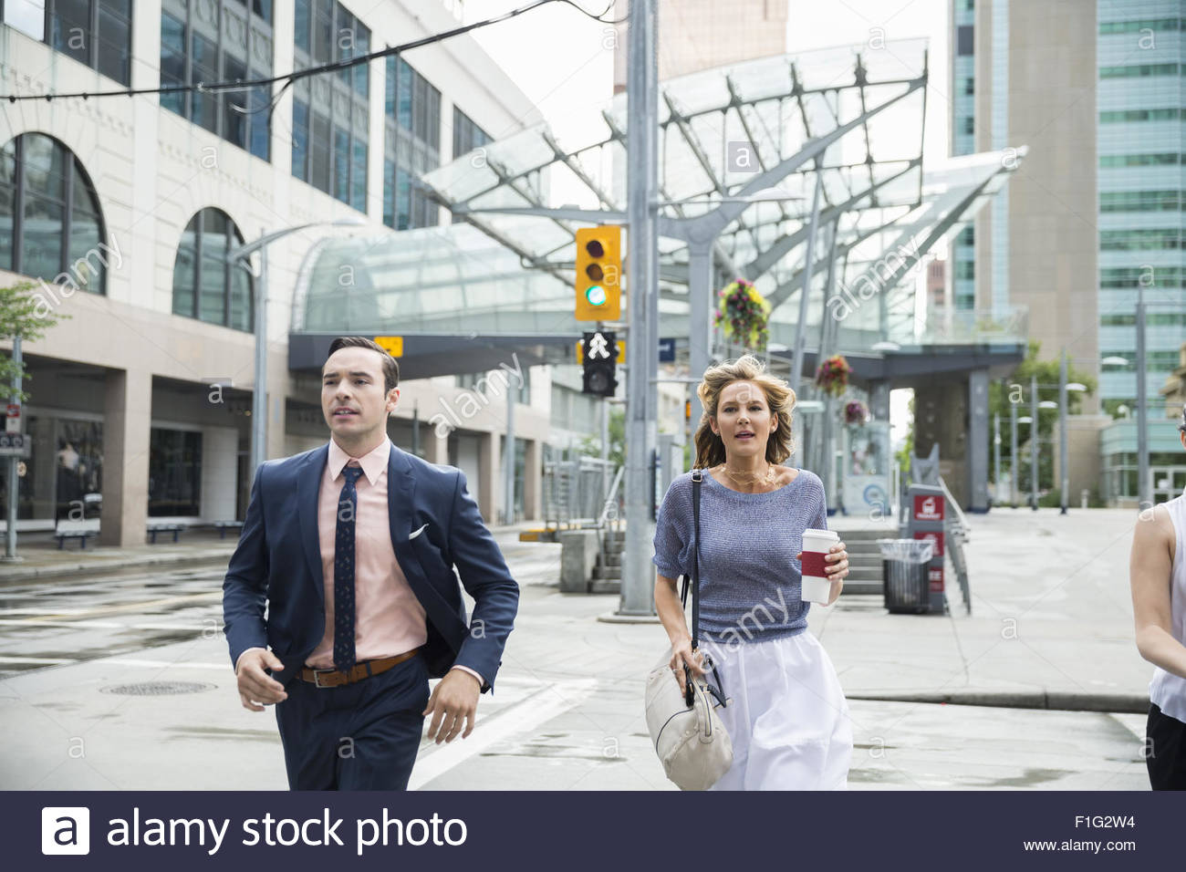 Business people rushing in crosswalk on urban street - Stock Image