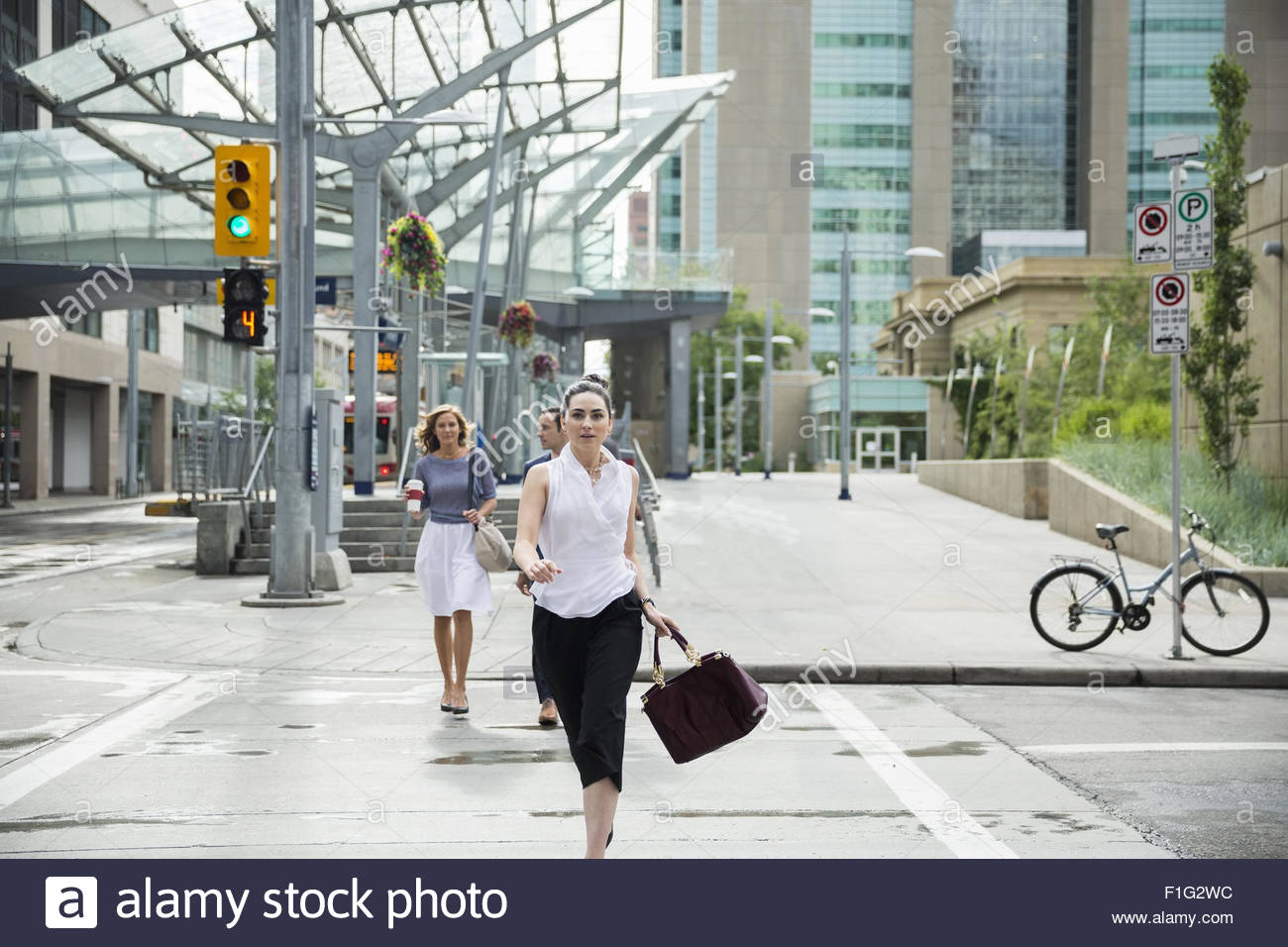 Businesswoman rushing in crosswalk in urban street - Stock Image