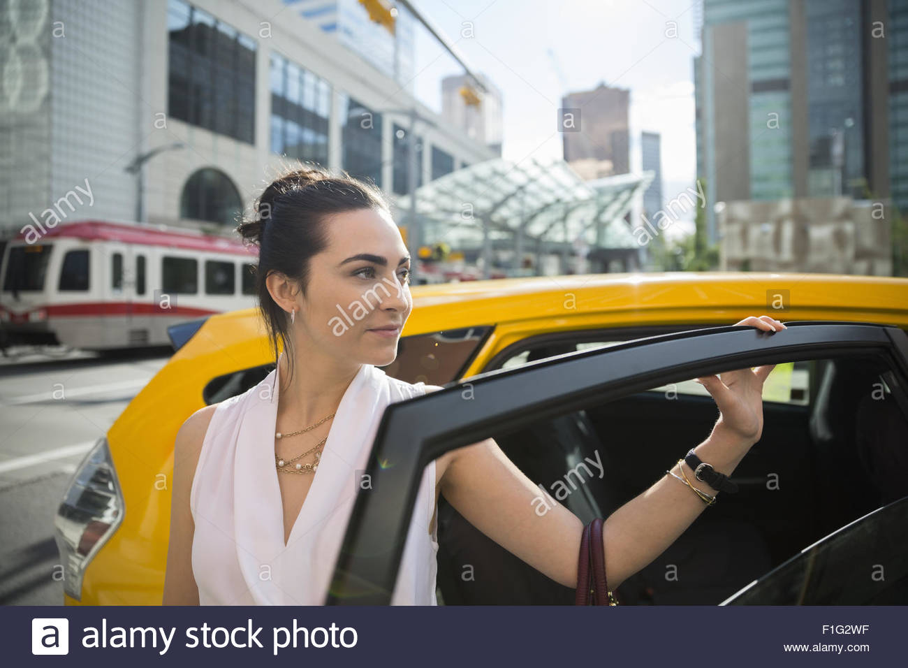 Businesswoman getting out of taxi in city - Stock Image