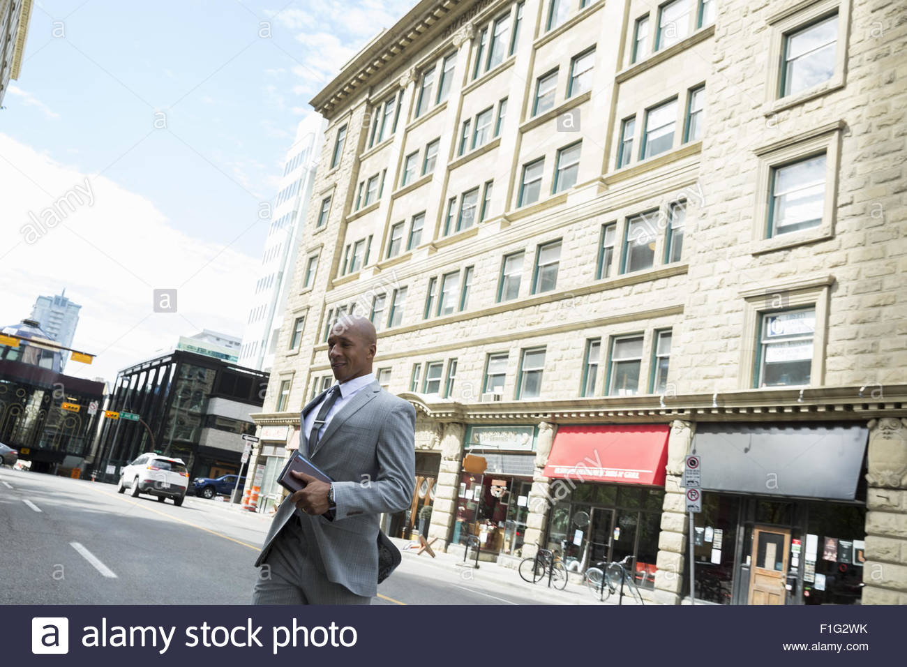 Businessman crossing urban street - Stock Image
