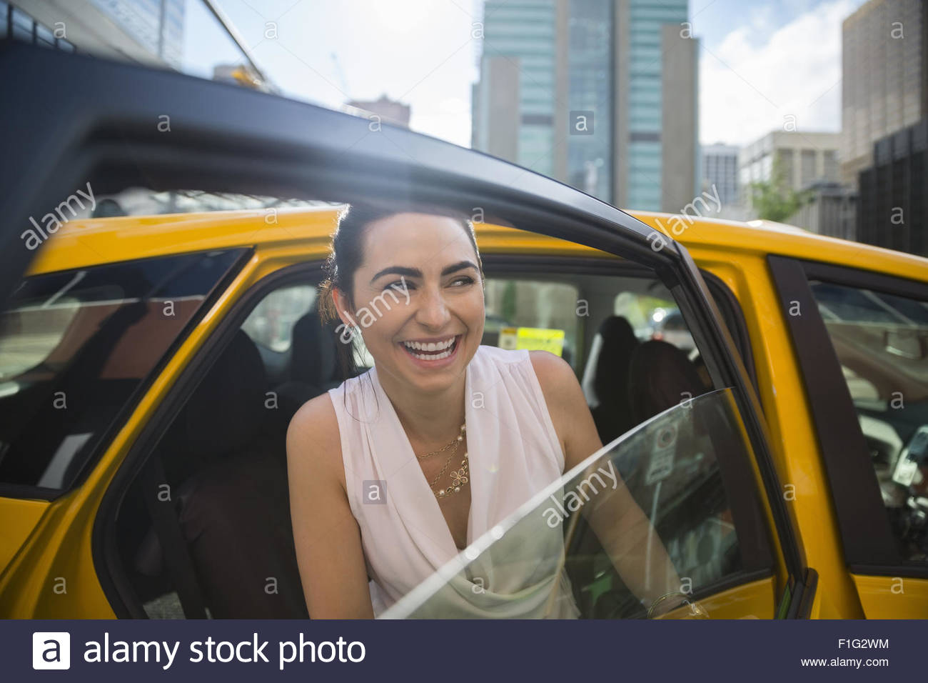 Smiling businesswoman getting out of taxi in city - Stock Image