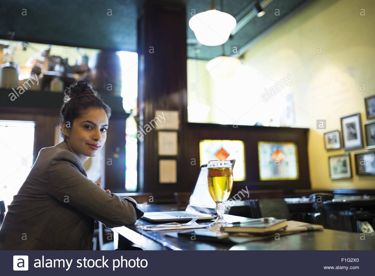 Portrait confident businesswoman working at laptop in pub - Stock Image