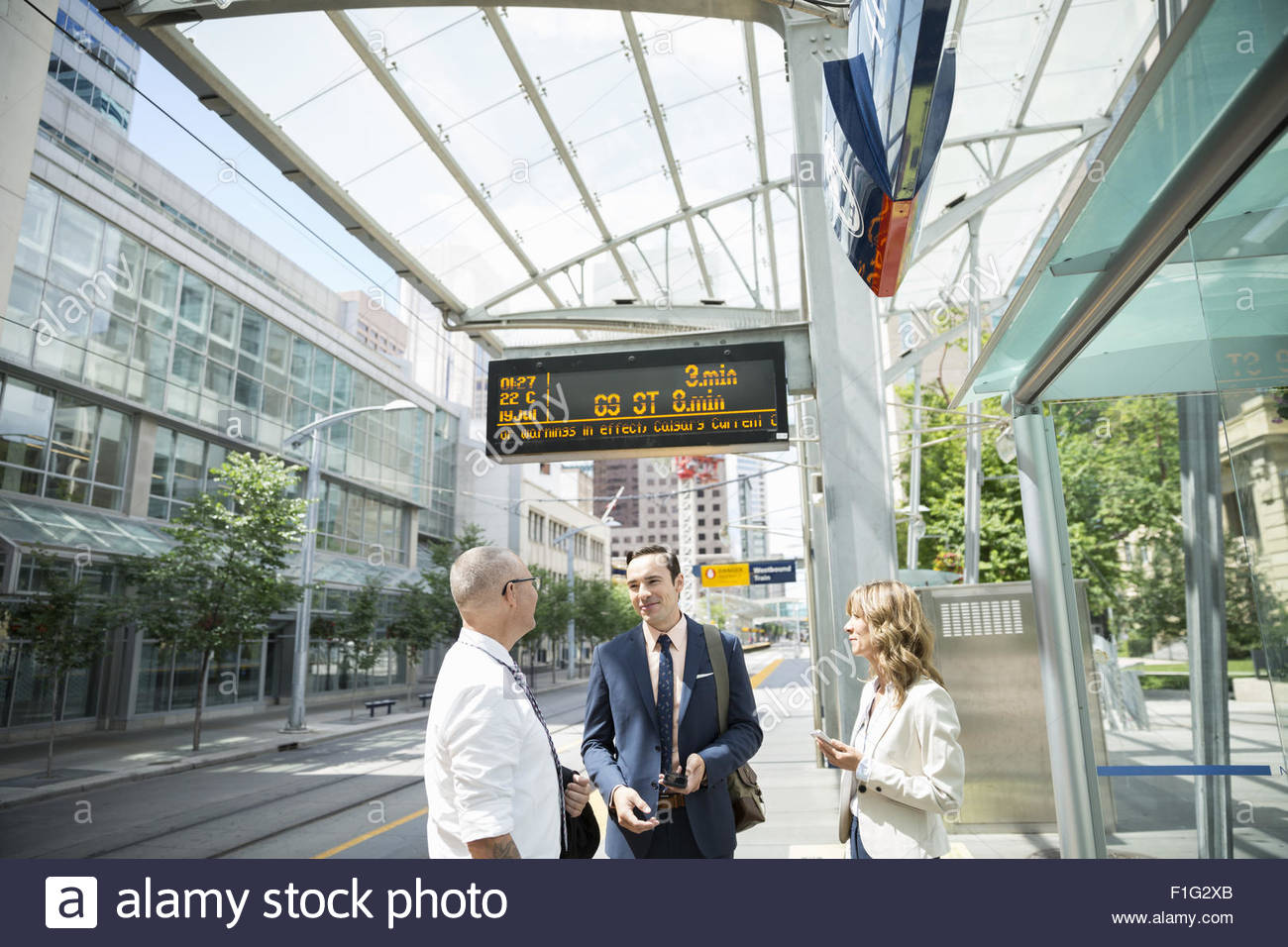 Business people talking on train station platform - Stock Image