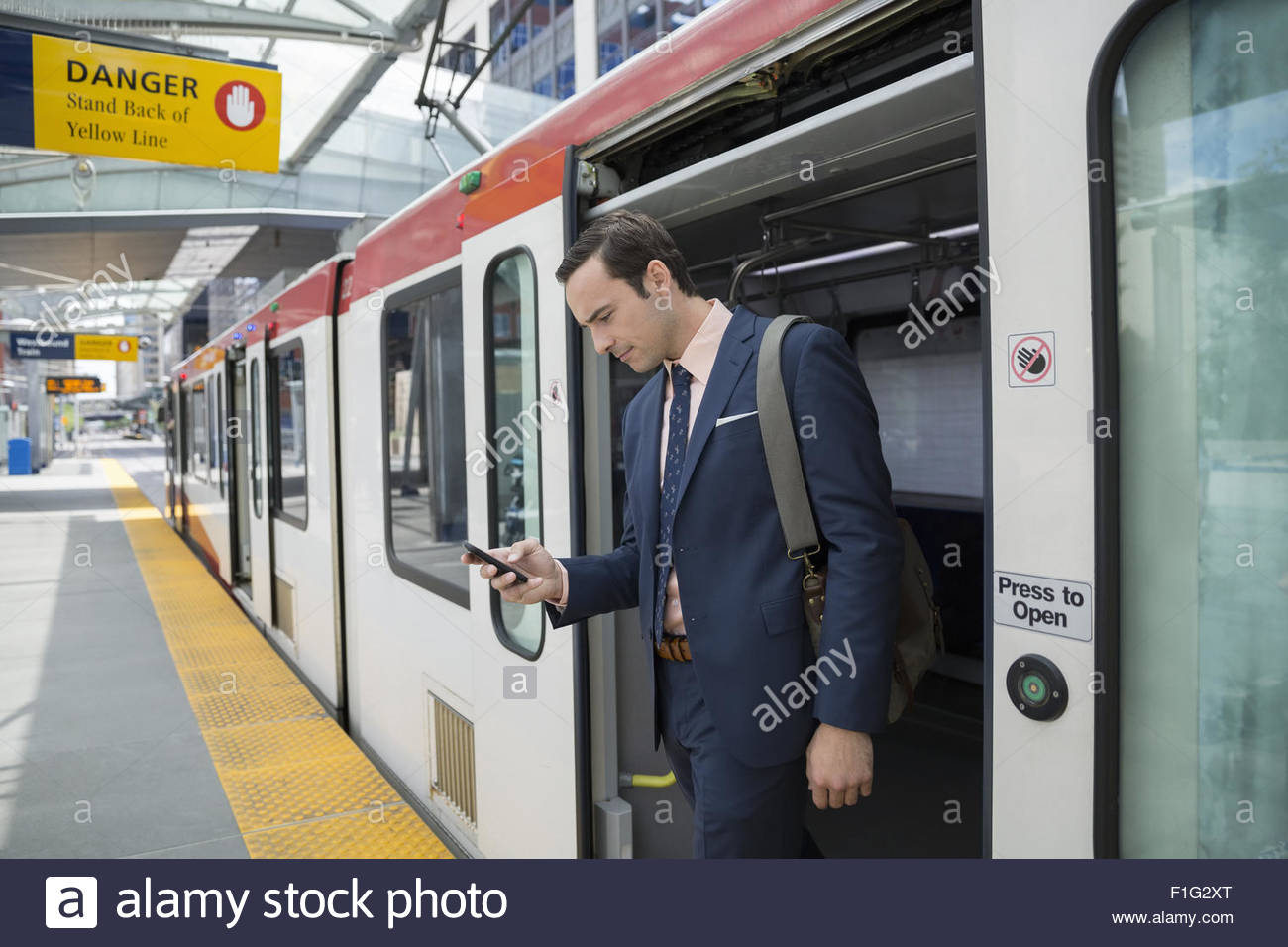 Businessman disembarking train texting with cell phone - Stock Image
