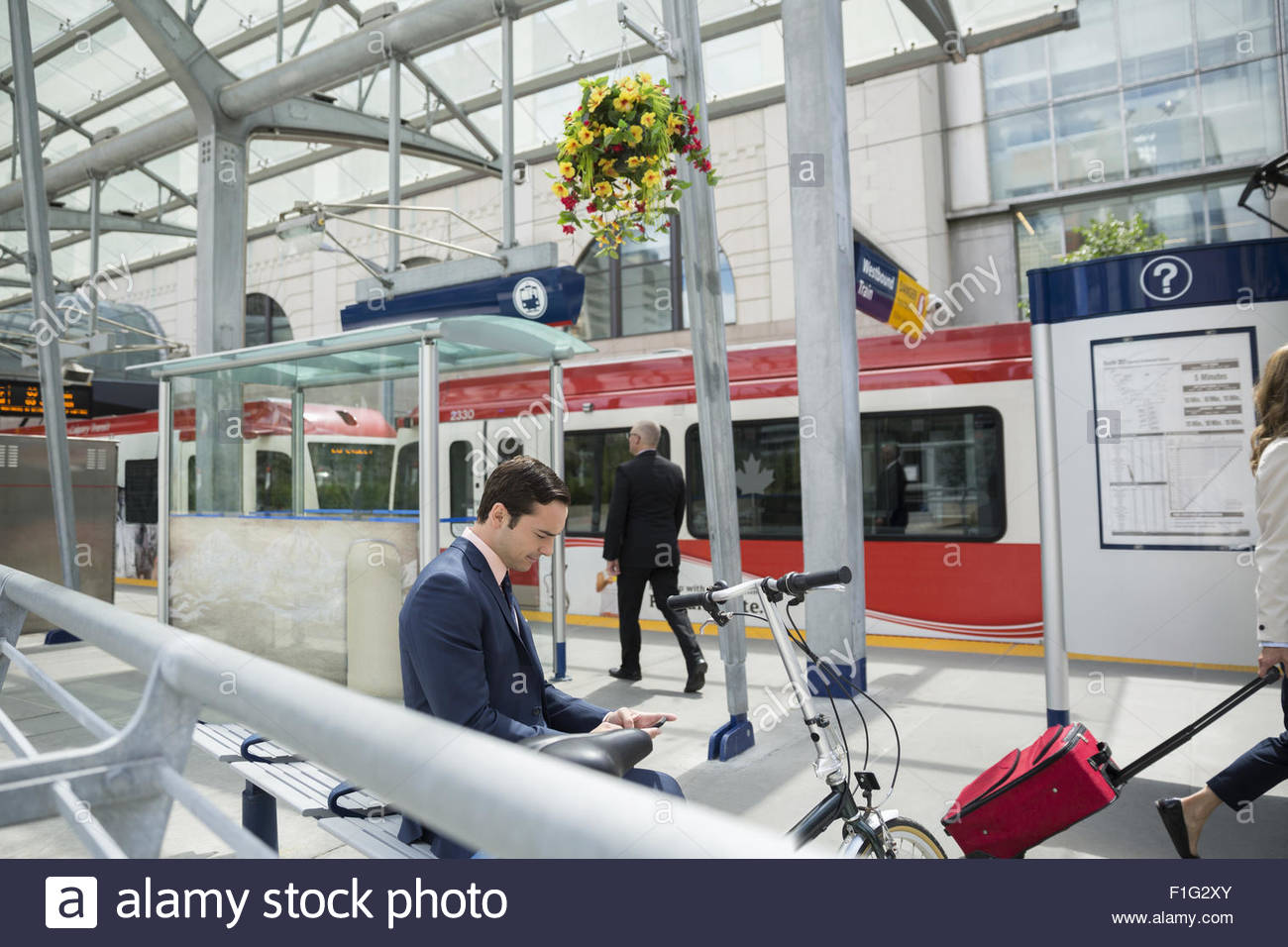 Businessman texting with cell phone at trains station - Stock Image