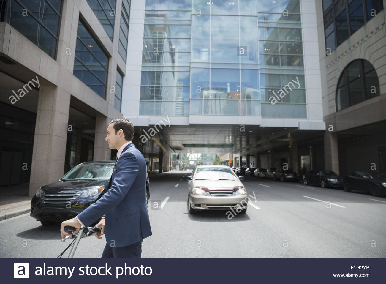 Businessman crossing city street - Stock Image