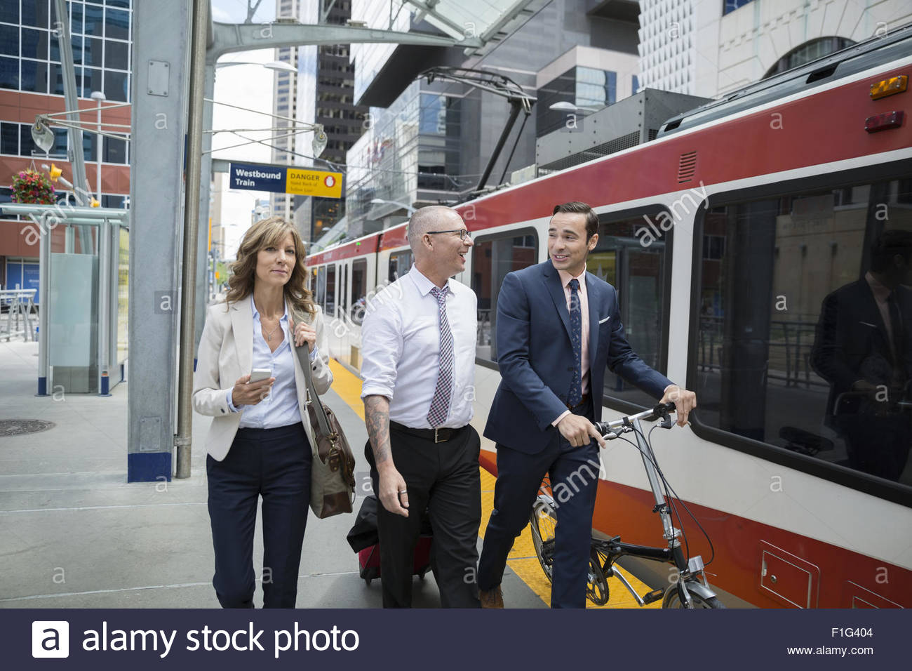 Business people walking along train station platform - Stock Image