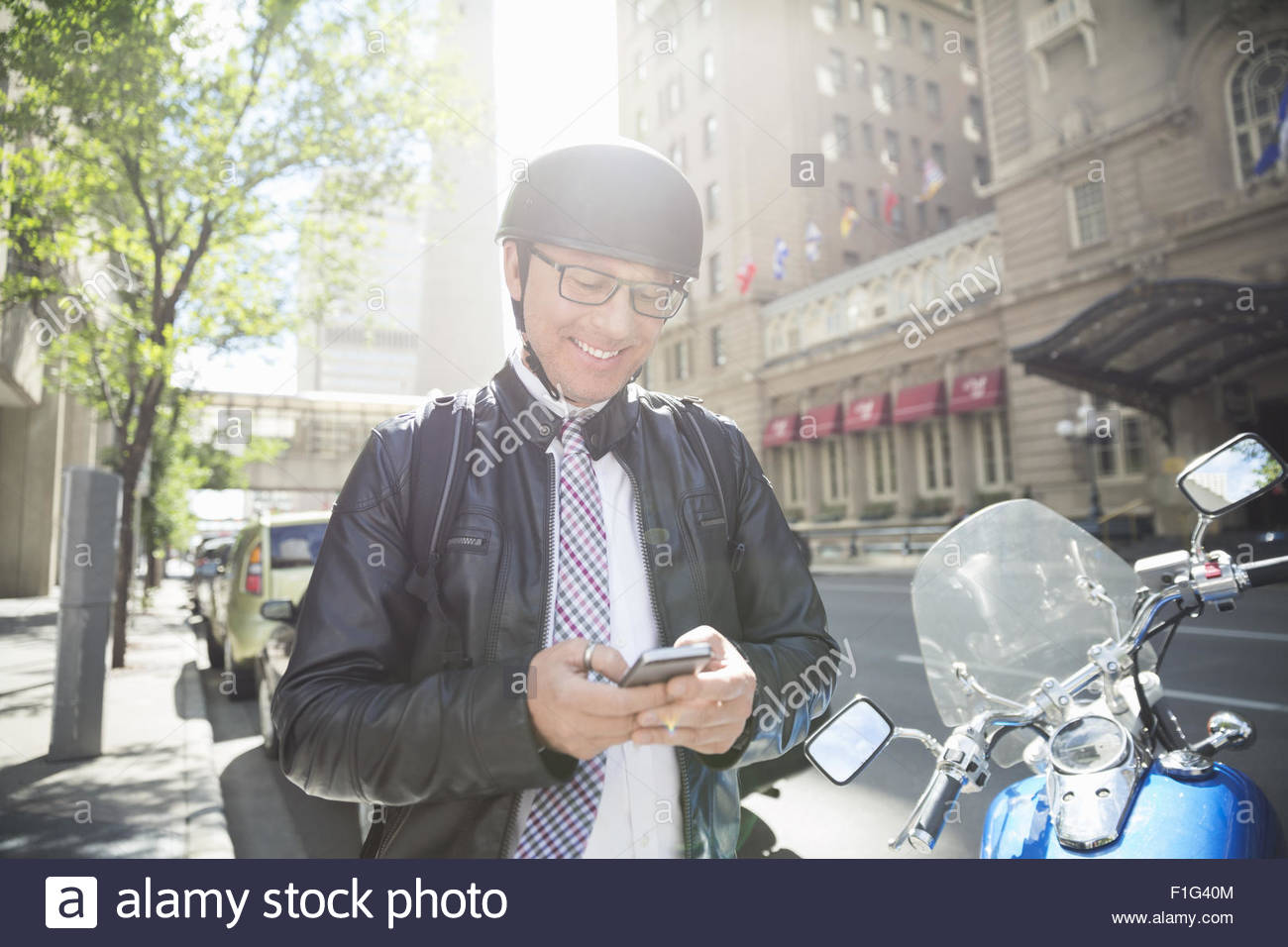 Businessman commuting on motorcycle texting with cell phone - Stock Image