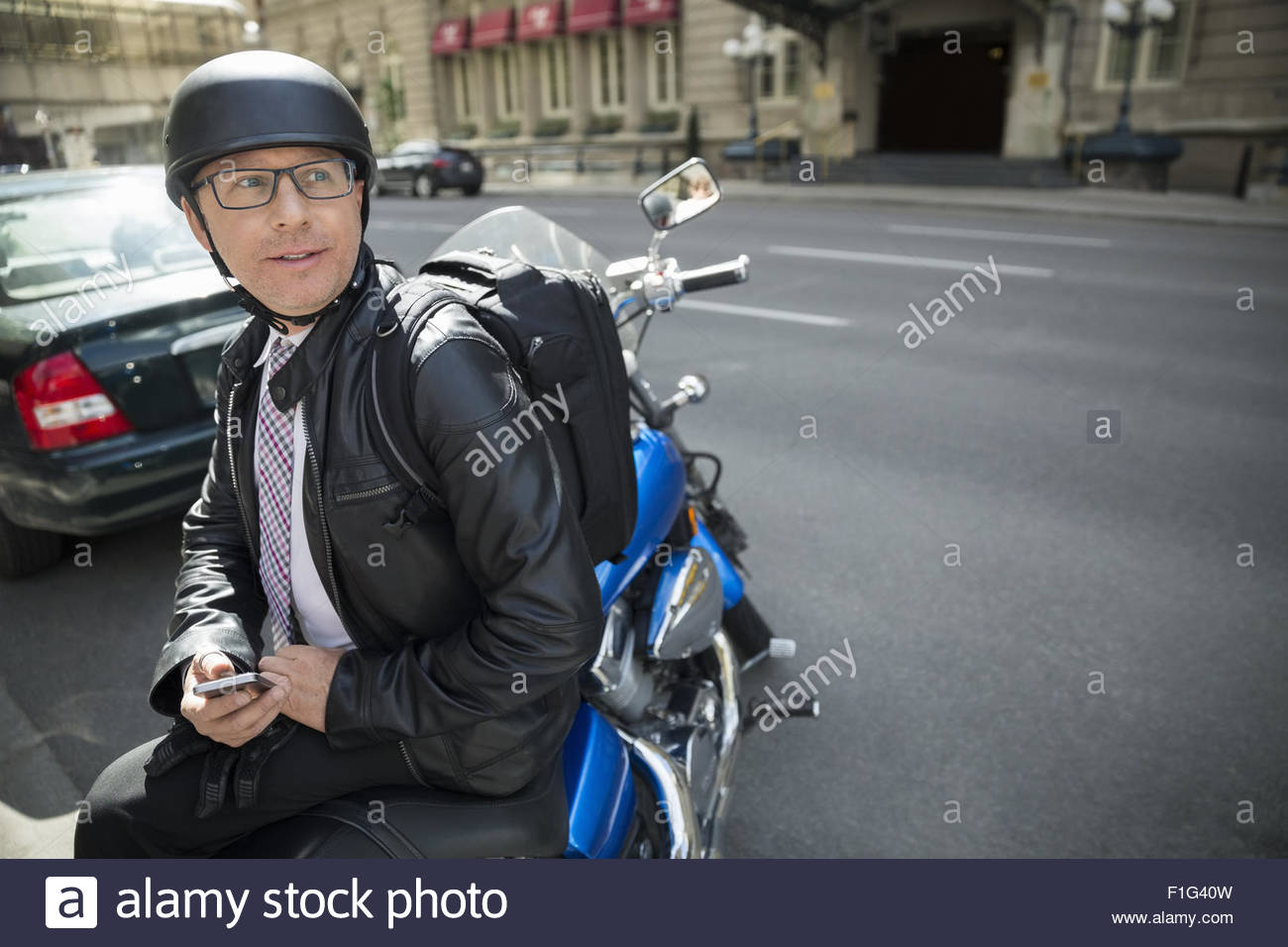 Businessman commuting on motorcycle - Stock Image